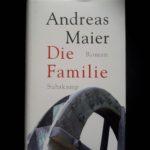 """Cover zu """"Die Familie"""" von Andreas Maier. Zu sehen ist der Ausschnitt eines Mühlrads in schwarz-weiß, der Hintergrund ist weiß. Der Buchtitel in roter Schrift darüber."""