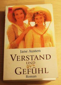 Buchcover von Jane Austen: Verstand und Gefühl. Auf dem Titelbild sind zwei blond Frauen zu sehen, die in die Kamera lächeln. Sie tragen Sommerkleider und beide einen Hut.