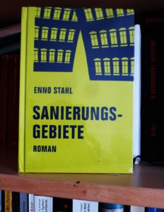"""Cover von """"Sanierungsgebiete"""" von Enno Stahl. Zzu sehen ist der Umriss eines Industriegebäudes auf den Kopf gestellt, dunkelblau auf grell-gelbem Hintergrund"""