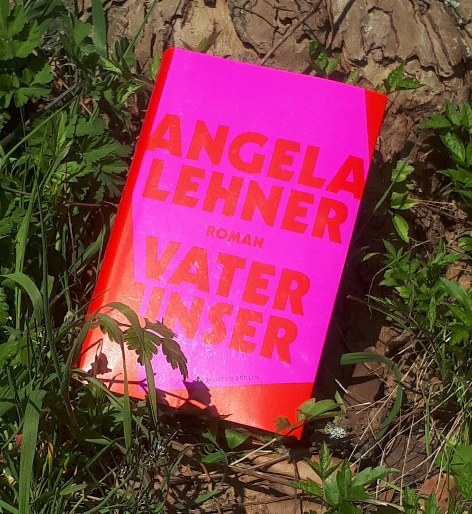 """Das Cover von """"Vater unser"""" von Angela Lehner schreit in grellem Rot und Pink und ist bei der leichten Sonneneinstrahlung im Foto kaum noch zu lesen. Die Schrift ist in Kapitälchen gehalten."""